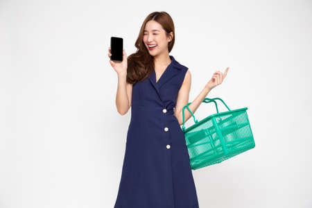 Beautiful Asian woman smiling and holding shopping basket and mobile phone isolated on white background 免版税图像