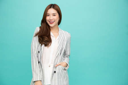 Portrait of successful business asian woman in suit and smile isolated over green background, Young businesswoman smiling and looking at camera, Happy feeling concept 免版税图像