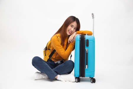 Young Asian woman traveler with backpack sitting on floor with suitcases isolated on white background