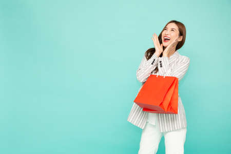 Portrait of excited screaming young asian woman holding shopping bag isolated over green background, Wow and surprised concept
