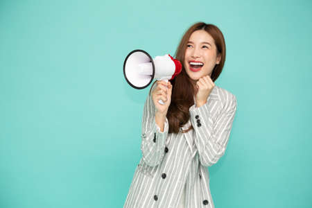 Young Asian woman holding megaphone isolated on green background, Speech and announce concept