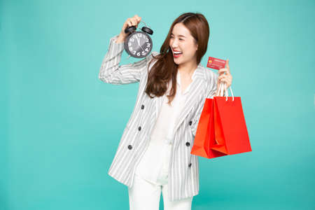 Midnight sale, Portrait of a happy young woman holding shopping bags and black alarm clock, Year end sale or mid year sale promotion clearance for Shopaholic concept, Asian female model