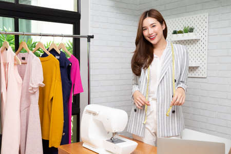 Asian beautiful young fashion designer woman with sewing machine in workroom, Dressmaker concept