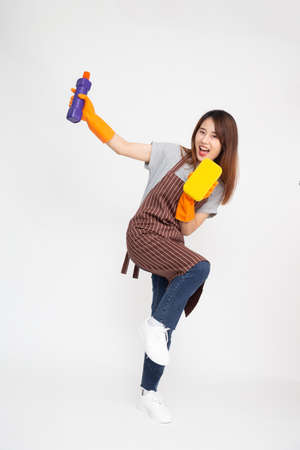 Portrait of young Asian woman wearing orange rubber gloves for hands protection and holding cleaning products and yellow sponge isolated over white background Reklamní fotografie