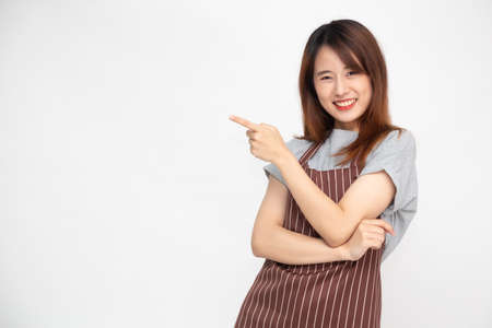 Portrait of Asian woman workers fresh market with brown apron standing and pointing finger to something isolated on white background