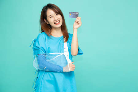 Young Asian beautiful woman wearing patient outfits and put on a soft splint due to a broken arm and holding credit card isolated on green background, Personal accident concept