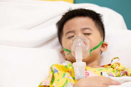 Asian little boy making inhalation with nebulizer at hospital, Nebulization concept