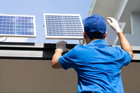 Asian workers technicians man installing solar photovoltaic panels for LED lamps on the roof of the house. Exterior solar cell system installation concept 免版税图像