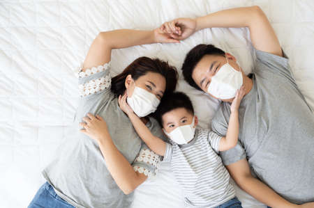 Top view of cute little boy and his asian parents looking at camera and wearing protective medical mask for prevent virus while lying on the white bed at home, Happy Family concept Reklamní fotografie