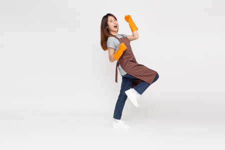 Portrait of young Asian woman standing and wearing orange rubber gloves for hands protection during cleaning isolated over white background