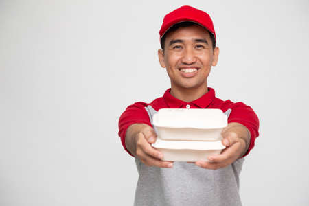 Food delivery man holding food box isolated on white background, Delivering food or parcel express service concept 免版税图像