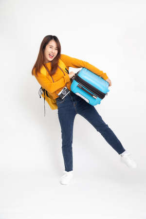Young Asian woman traveler with backpack standing and holding suitcases isolated on white background