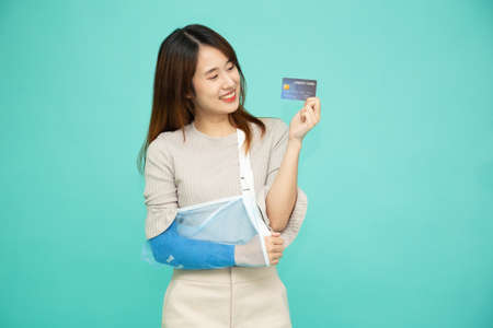 Young Asian woman put on a soft splint due to a broken arm and holding credit card isolated on green background, Personal accident concept 免版税图像