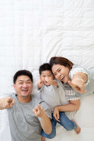 Top view of cute little boy and his asian parents smiling and pointing finger to something while lying on the white bed at home, Happy Family concept