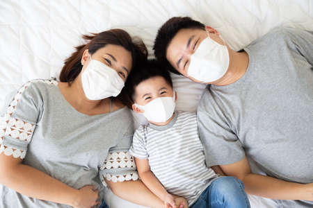 Top view of cute little boy and his asian parents looking at camera and wearing protective medical mask for prevent virus while lying on the white bed at home, Happy Family concept