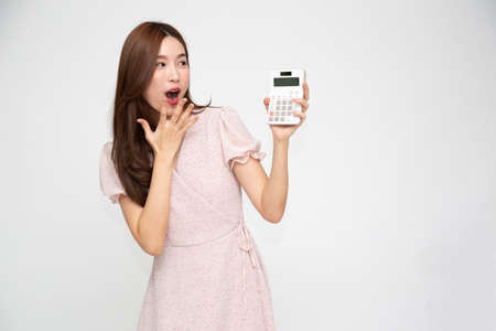 Portrait of excited Asian woman holding calculator isolated on white background, Wow and surprised concept