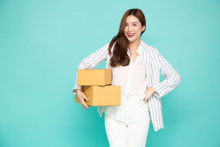 Happy Asian woman smiling and holding package parcel box isolated on light green background, Delivery courier and shipping service concept