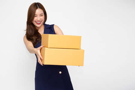 Happy Asian woman smiling and holding package parcel box isolated on white background, Delivery courier and shipping service concept