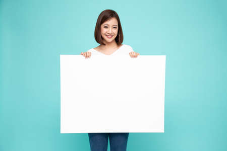 Young asian woman showing and holding blank white billboard isolated on green background Imagens