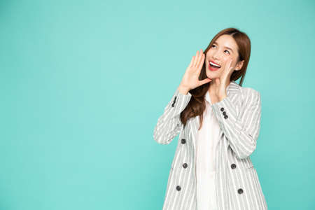 Portrait of excited screaming young asian woman isolated over green background, Wow and surprised concept