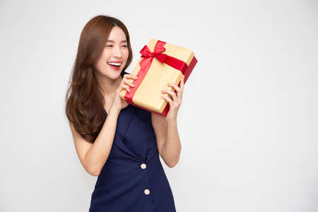 Happy beautiful Asian woman smile with gold gift box isolated on white background. Teenage girls in love, Receiving gifts from lovers. New Year, Christmas and Valentines Day concept Stock Photo