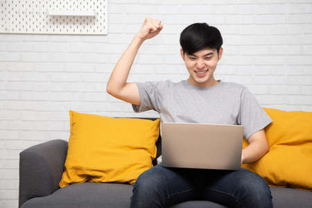 Young Asian man is browsing at his laptop and raising his arm up with celebrating success on sofa at home
