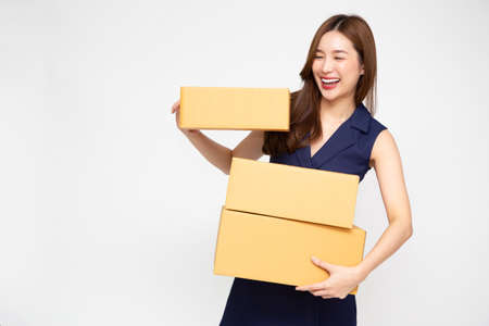 Happy Asian woman smiling and holding package parcel box isolated on white background, Delivery courier and shipping service concept Stock Photo