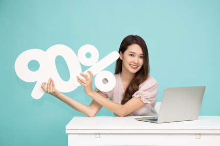 Portrait of Asian business woman showing and holding 90% number or ninety percent and sitting with laptop isolated over light green background Stock Photo