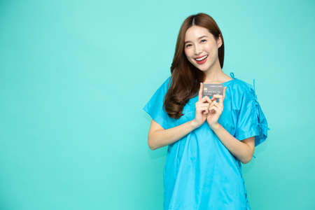 Young Asian beautiful woman patient holding credit card isolated on green background Banque d'images