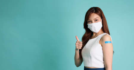 Beautiful Asian woman wearing face mask and showing thumbs up and arm with plaster or bandage of Vaccinated isolated on green background