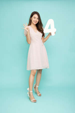 Young beautiful Asian woman showing number 4 and pointing up with finger number four isolated on green background