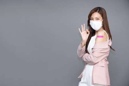 Beautiful Asian woman wearing face mask and showing ok sign and arm with plaster or bandage of Vaccinated isolated on grey background
