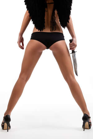 sexy halloween: Dark Angel, a sexy woman with a knife and black angel wings against a white backround Stock Photo