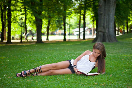 laying down: Beautiful young girl reading a book