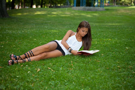 Beautiful young girl reading a book photo
