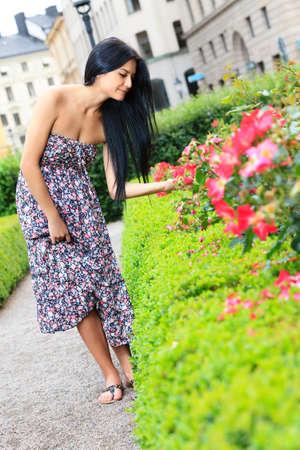 Mujer joven mirando las flores en el jardín de la ciudad