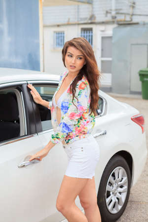 Young woman opening a car door photo