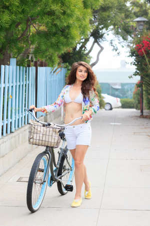 Young woman walking with a bicycle photo