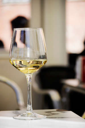 Close-up of a glass of white wine on a bar's table outside. Background out of focus