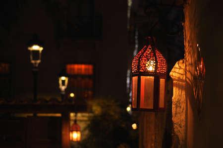 Spanish street lantern hanging on an old wall lighting dimly