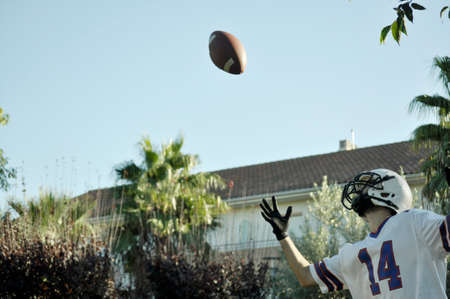 American football player in a game. Player catching an American football ball in a park.