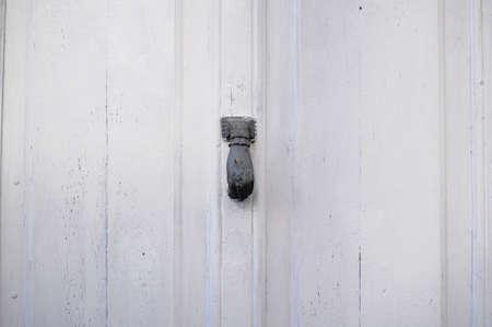 Door handle with hand shape. Handle in an antique white door