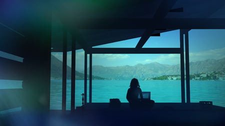 Silhouette of a blogger sitting in a paradise place and working on the computer Stock Photo