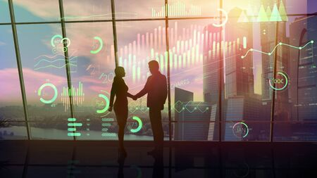 Silhouettes of a businessman and a businesswoman at the time of a handshake.