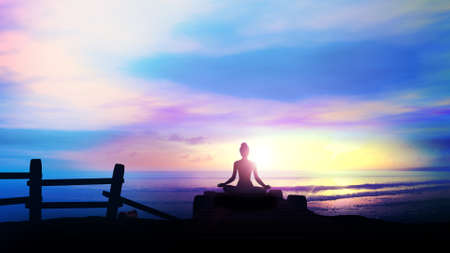Silhouette of a woman meditating at dawn. 版權商用圖片