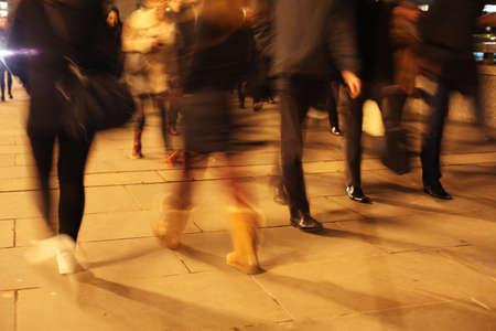Commuters at night on London Bridge, London, England