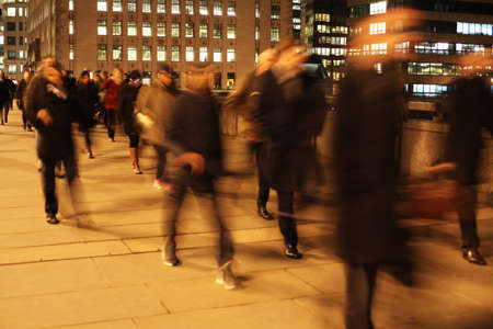 Commuters at night on London Bridge, London, England. 写真素材
