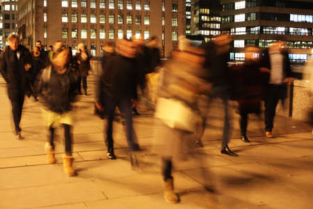 Commuters at night on London Bridge, London, England. Banque d'images