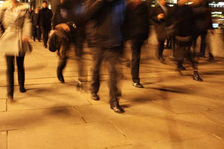 Commuters at night on London Bridge, London, England. Standard-Bild