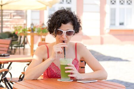 Brunette with curly hair, drinking a mint lemonade in the shade at terrace photo